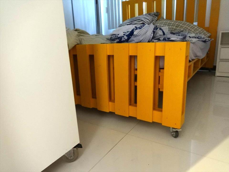 yellow painted pallet bed on wheels